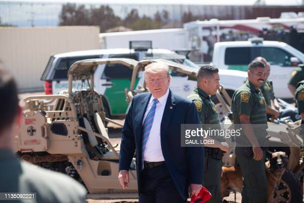 US President Donald Trump speaks with members of the US Customs and Border Patrol as he tours the border wall between the United States and Mexico in...