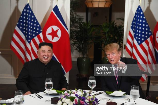 President Donald Trump speaks with North Korea's leader Kim Jong Un as they sit for a dinner at the Sofitel Legend Metropole hotel in Hanoi on...