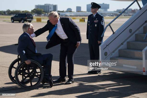 US President Donald Trump speaks with Texas Governor Greg Abbott as he arrives at Dallas Love Field in Dallas Texas on October 25 2017 / AFP PHOTO /...