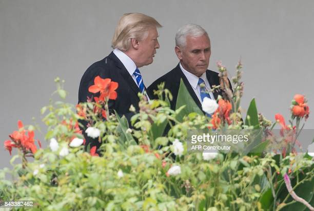 US President Donald Trump speaks with Vice President Mike Pence as they walk through the colonnade before Trump departs for North Dakota at the White...