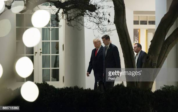 S President Donald Trump speaks with White House Secretary Rob Porter and Sen Mike Lee as they return to the White House December 4 2017 in...