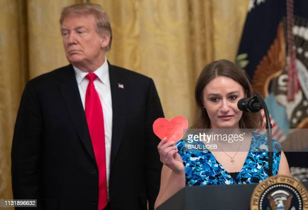 President Donald Trump stands alongside Polly Olson , a student of Northeast Wisconsin Technical College, as she holds up a Valentine's Day card that...