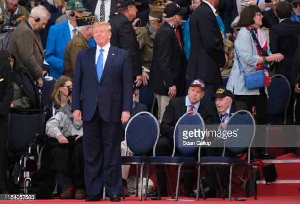 S President Donald Trump stands as American Battle of Normandy veterans and family members look on during the main ceremony to mark the 75th...
