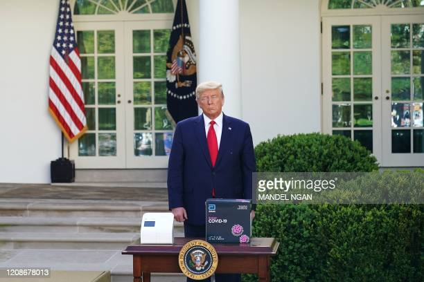 President Donald Trump stands behind a 5-minute test for COVID-19 from Abbott Laboratories during the daily briefing on the novel coronavirus,...