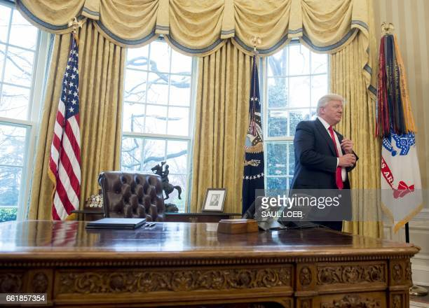 President Donald Trump stands behind the Resolute Desk after speaking about signing executive orders on trade policies in the Oval Office of the...