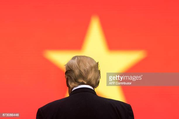 US President Donald Trump stands during an arrival ceremony in Hanoi on November 12 2017 Trump arrived in the Vietnamese capital on November 11 after...