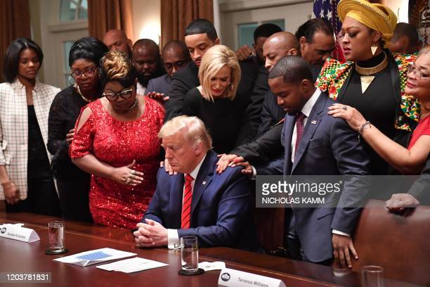 President Donald Trump stands in a prayer circle with African-American leaders in the Cabinet Room of the White House in Washington, DC, on February...