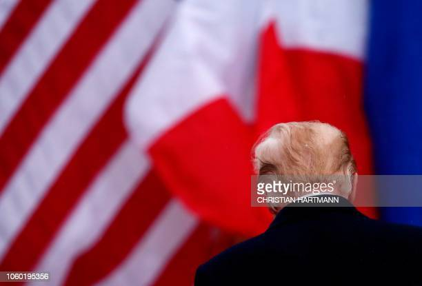 US President Donald Trump stands in front of an American and a French flag as he visits the American Cemetery of Suresnes outside Paris on November...