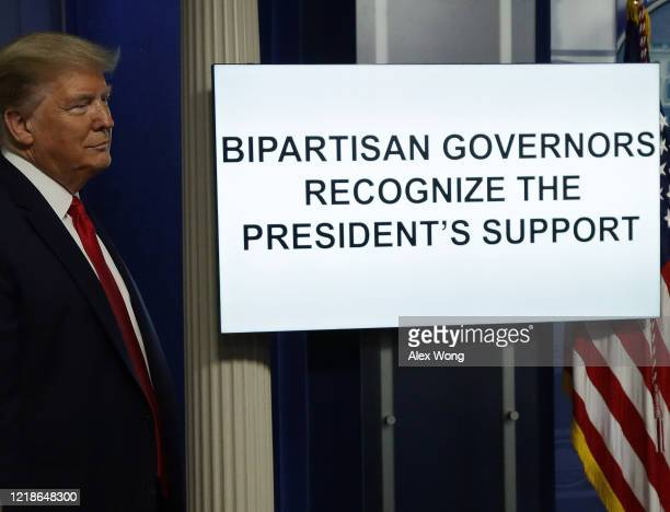 President Donald Trump stands next to a monitor playing a video during the briefing of the White House Coronavirus Task Force in the James Brady...