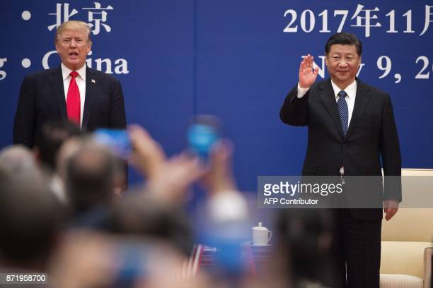 US President Donald Trump stands next to China's President Xi Jinping during a business leaders event at the Great Hall of the People in Beijing on...