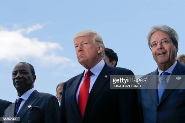 US President Donald Trump stands next to Italian Prime Minister Paolo Gentiloni and Guinea's President Alpha Conde during a family photo with African...