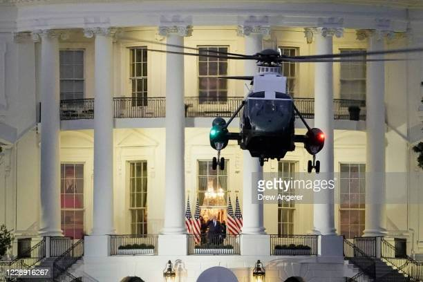 President Donald Trump stands on the Blue Room Balcony as Marine One, takes off from the South Lawn of the White House on October 5, 2020 in...