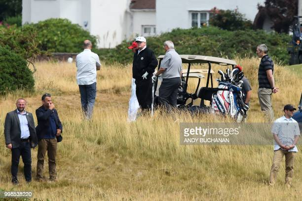 US President Donald Trump stands on the first green as he plays a round of golf on the Ailsa course at Trump Turnberry the luxury golf resort of US...