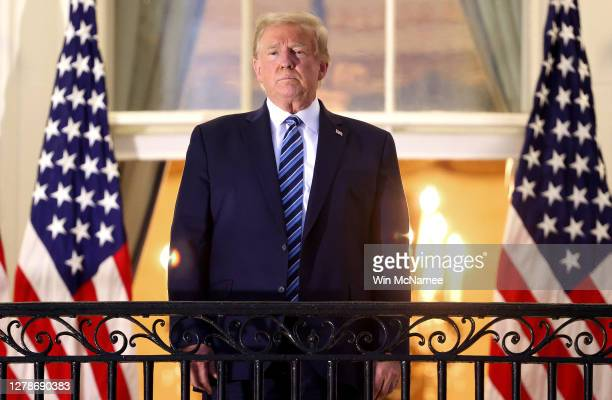 President Donald Trump stands on the Truman Balcony after returning to the White House from Walter Reed National Military Medical Center on October...
