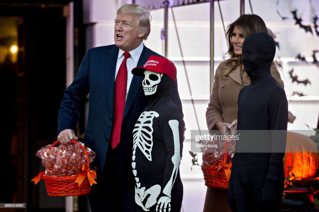 U.S. President Donald Trump stands with a child wearing a 'Make America Great Again' hat and skeleton costume next to U.S. First Lady Melania Trump, right, during a Halloween event on the South Lawn of the White House in Washington, D.C., U.S., on Monday, Oct. 30, 2017. Trump greeted costumed children during a traditional Halloween trick-or-treat at the White House, on the same day as Special Counsel Robert Mueller's investigation took a major turn as authorities charged three people -- a former campaign chief, his business associate and an ex-policy adviser -- with crimes including money laundering, lying to the FBI and conspiracy. Photographer: Andrew Harrer/Bloomberg via Getty Images