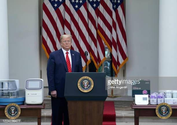 S President Donald Trump stands with COVID19 testing equipment during a press briefing about coronavirus testing in the Rose Garden of the White...