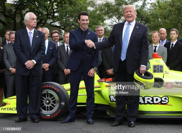 S President Donald Trump stands with Indianapolis 500 winning driver Simon Pagenaud and Team Penske owner Roger Penske during a ceremony to honor the...