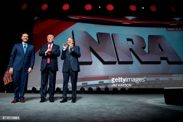 US President Donald Trump stands with National Rifle Association President Wayne LaPierre and NRAILA Executive Director Chris Cox during the NRA...