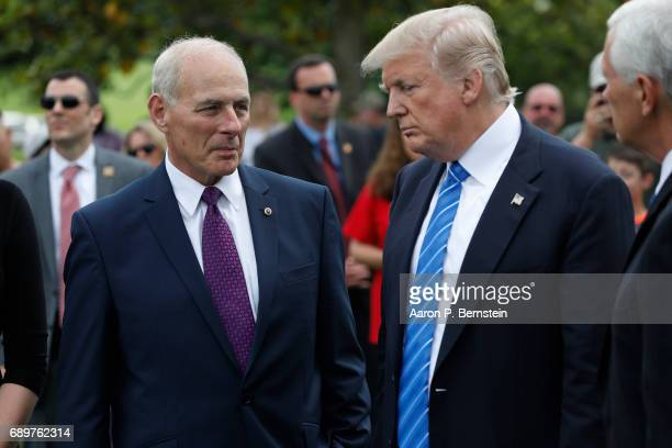 President Donald Trump stands with Secretary of Homeland Security John Kelly and Vice President Mike Pence after laying flowers on the grave of...