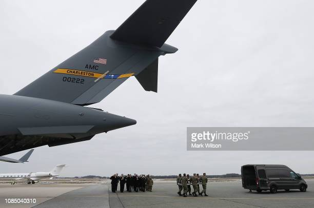 S President Donald Trump stands with the official party as a military carry team moves the transfer case containing the remains of Scott A Wirtz...