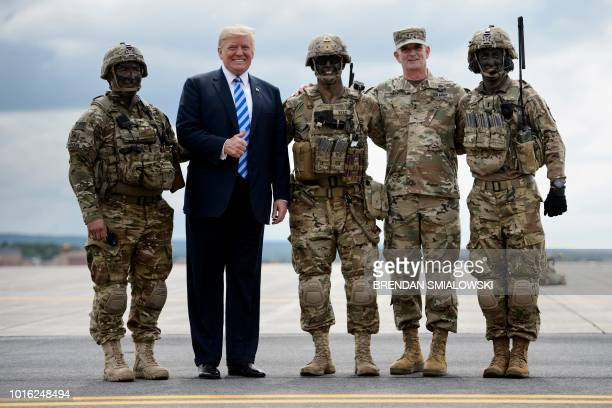 US President Donald Trump stands with troops after watching air assault exercise with Army Major General Walter Piatt at Fort Drum New York on August...