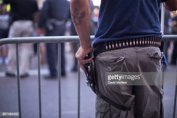 President Donald Trump supporter wears a gun while arguing with demonstrators outside the Phoenix Convention Center before a rally by Trump on August...
