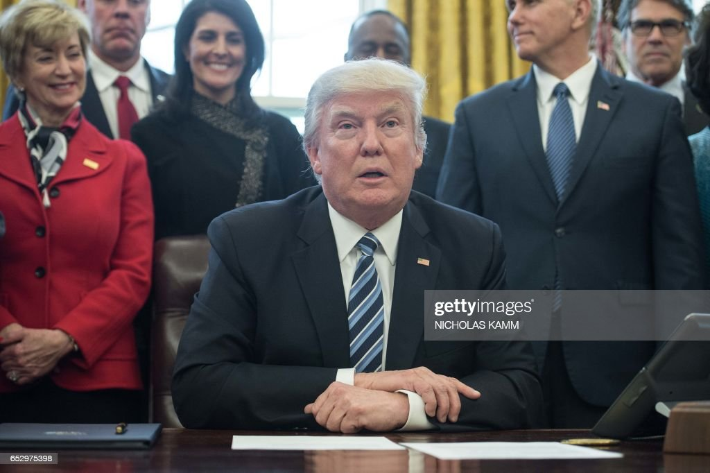 US President Donald Trump, surrounded by members of his cabinet, speaks before signing an executive order entitled Comprehensive Plan for Reorganizing the Executive Branch in the Oval Office at the White House in Washington, DC, on March 13, 2017. /