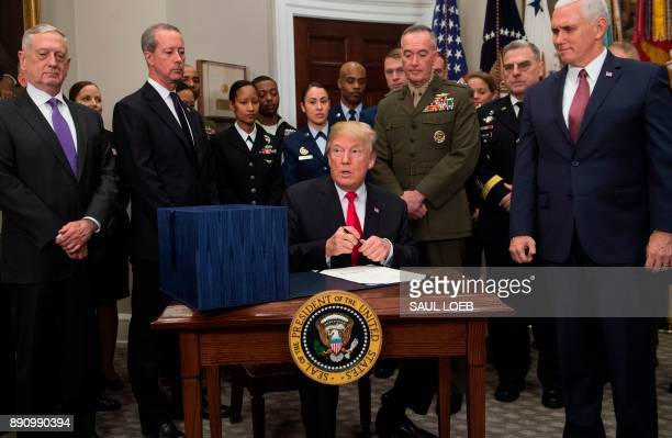 US President Donald Trump surrounded by military officials and members of Congress including Vice President Mike Pence and Secretary of Defense Jim...