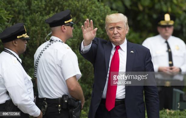 US President Donald Trump surrounded by Uniformed Division Secret Service officers waves after arriving on Marine One on the South Lawn of the White...