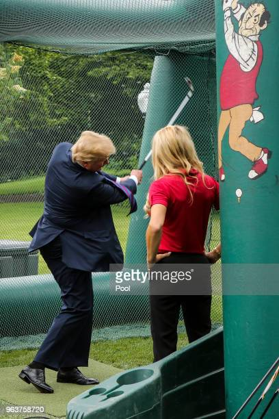 President Donald Trump swings a golf club during the White House Sports and Fitness Day on the South Lawn on May 30 2018 in Washington DC