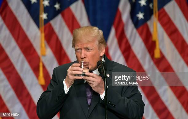 President Donald Trump takes a drink of water as he speaks about his administration's National Security Strategy at the Ronald Reagan Building and...
