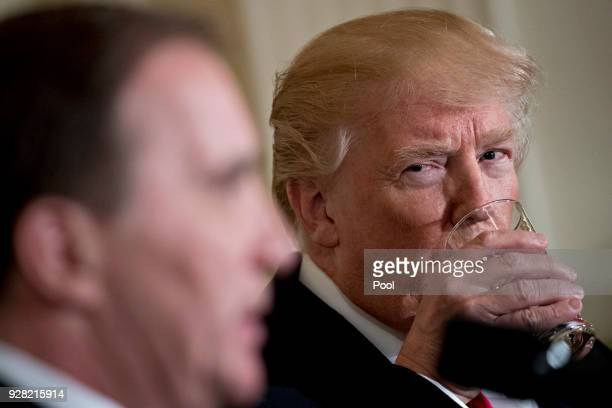 S President Donald Trump takes a drink of water as Stefan Lofven Sweden's prime minister left speaks during a joint news conference in the East Room...