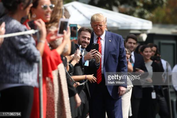 S President Donald Trump takes a photo with an onlooker as he returns to the White House after attending the United Nations General Assembly on...