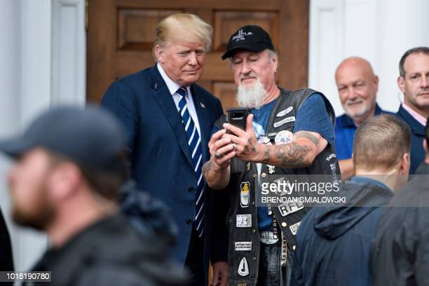 US President Donald Trump takes a selfie with a supporter during a Bikers for Trump event at the Trump National Golf Club August 11 2018 in...