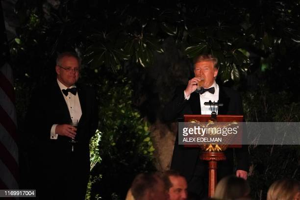 US President Donald Trump takes a sip of a drink alongside Australian Prime Minister Scott Morrison during an Official Visit with a State Dinner at...