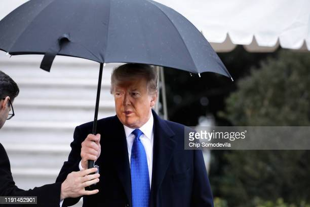 S President Donald Trump takes an umbrella from an aide as he walks out of White House December 02 2019 in Washington DC The president is traveling...