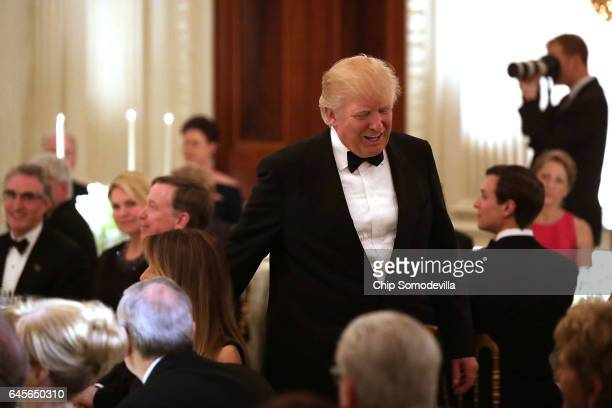 President Donald Trump takes his seat after giving a toast during the annual Governors' Dinner in the East Room of the White House February 26 2017...
