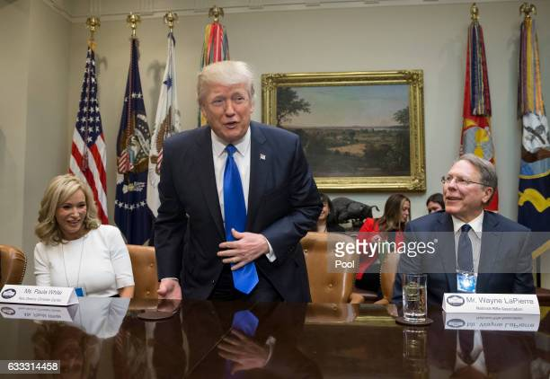 US President Donald Trump takes his seat between Paula White of the New Destiny Christian Center and Executive Vice President and CEO of the National...