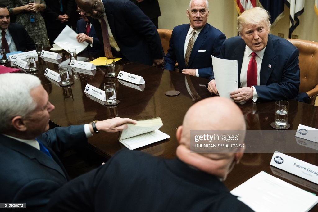 US President Donald Trump takes his seat for a meeting with health insurance executives in the Roosevelt Room of the White House on February 27, 2017 in Washington, DC. / AFP / Brendan Smialowski