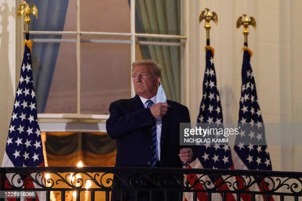 President Donald Trump takes off his facemask as he arrives at the White House upon his return from Walter Reed Medical Center, where he underwent...