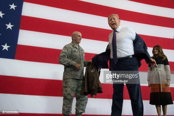 US President Donald Trump takes off his suit jacket to receive a bomber jacket from the US Pacific Air Forces as First Lady Melania Trump looks on...