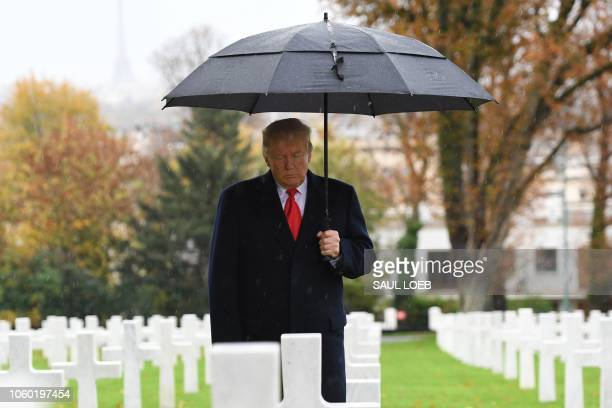 President Donald Trump takes part in a ceremony at the American Cemetery of Suresnes, outside Paris, on November 11, 2018 as part of Veterans Day and...