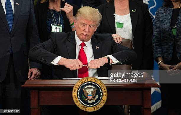 US President Donald Trump takes the cap off a pen to sign an executive order to start the Mexico border wall project at the Department of Homeland...