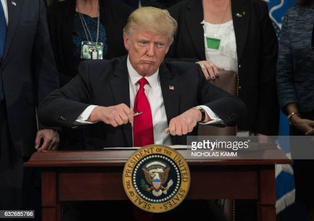 President Donald Trump takes the cap off a pen to sign an executive order to start the Mexico border wall project at the Department of Homeland...