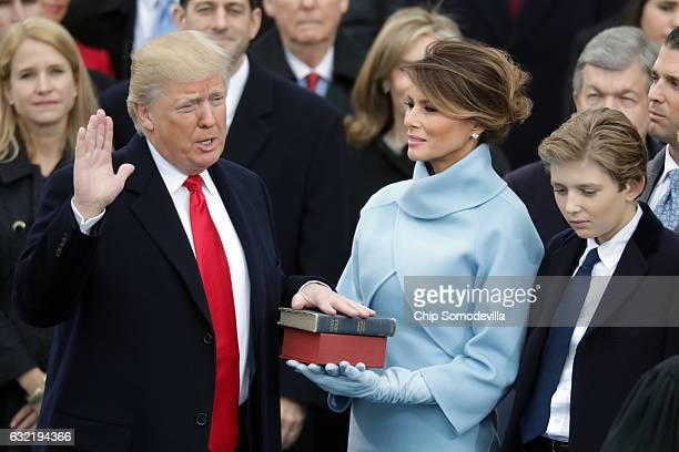 President Donald Trump takes the oath of office as his wife Melania Trump holds the bible and his son Barron Trump looks on, on the West Front of the...