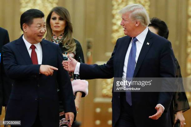 US President Donald Trump talks to China's President Xi Jinping in front of US First Lady Melania Trump as they arrive for a state dinner at the...