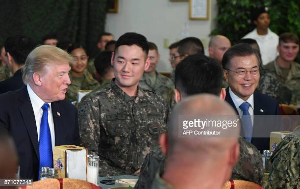 US President Donald Trump talks to military personnel while South Korean President Moon JaeIn looks on at Camp Humphreys in Pyeongtaek south of Seoul...