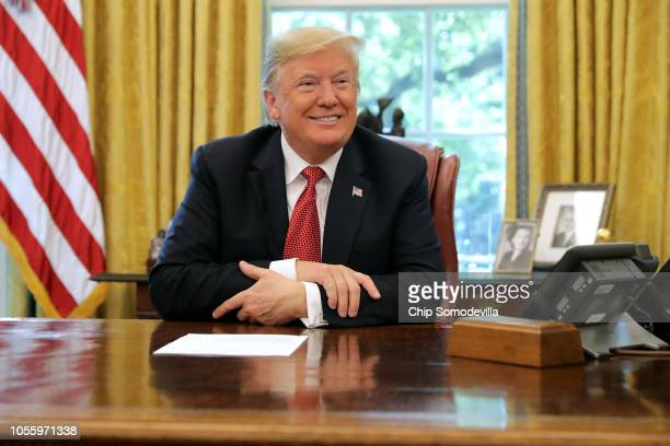 President Donald Trump talks to reporters while hosting workers and members of his cabinet for a meeting in the Oval Office at the White House...