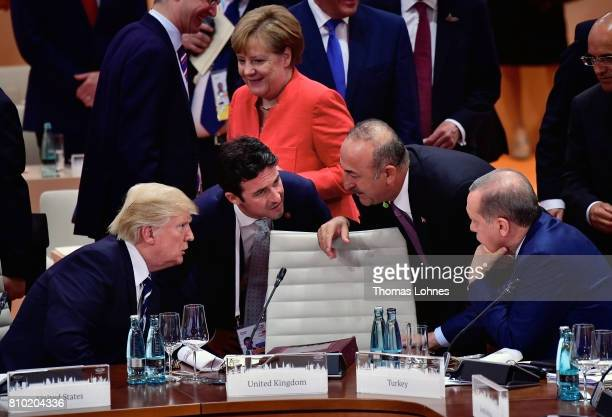 S President Donald Trump talks to the President of Turkey Recep Tayyip Erdogan while German Chancellor Angela Merkel is seen in the background before...