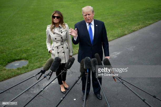 President Donald Trump talks to the press flanked by First Lady Melania Trump as he prepares to board Marine One for Beltsville, Maryland, in...